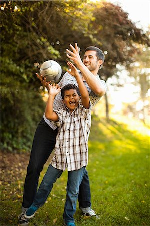 Father and son playing soccer together Stock Photo - Premium Royalty-Free, Code: 614-06536731