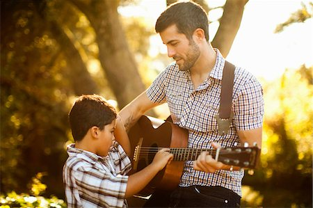 Father and son playing guitar together Stock Photo - Premium Royalty-Free, Code: 614-06536733