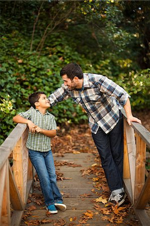 Father and son playing on wooden bridge Stock Photo - Premium Royalty-Free, Code: 614-06536742