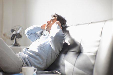 Man listening to headphones on sofa Stock Photo - Premium Royalty-Free, Code: 614-06536756