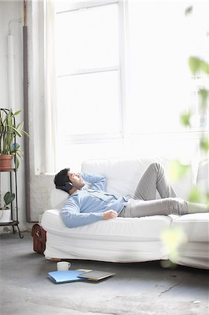Man listening to headphones on sofa Stock Photo - Premium Royalty-Free, Code: 614-06536759