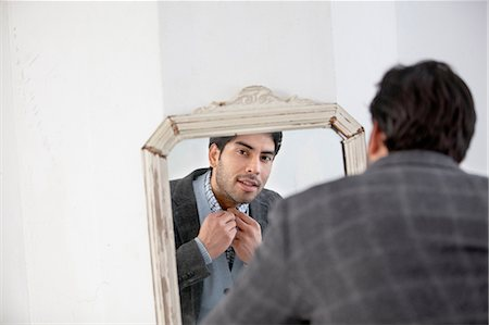 Man examining himself in mirror Stock Photo - Premium Royalty-Free, Code: 614-06536774