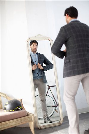 Man examining himself in mirror Stock Photo - Premium Royalty-Free, Code: 614-06536773