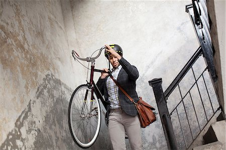 Man carrying bicycle down staircase Stock Photo - Premium Royalty-Free, Code: 614-06536789