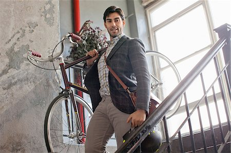 Man carrying bicycle down staircase Stock Photo - Premium Royalty-Free, Code: 614-06536794