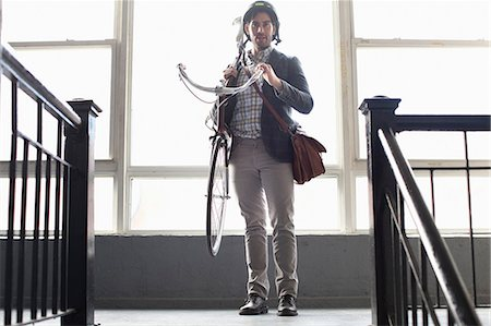 Man carrying bicycle on staircase Stock Photo - Premium Royalty-Free, Code: 614-06536790
