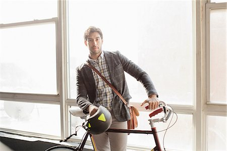 Man standing with bicycle by window Stock Photo - Premium Royalty-Free, Code: 614-06536791
