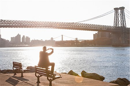 people sitting on bench - Man taking pictures of urban bridge Stock Photo - Premium Royalty-Free, Code: 614-06536805