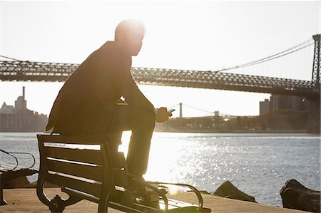 people sitting on bench - Man using cell phone by urban bridge Stock Photo - Premium Royalty-Free, Code: 614-06536807