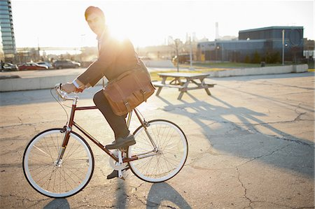 Man riding bicycle on city street Stock Photo - Premium Royalty-Free, Code: 614-06536825