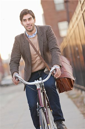 Man riding bicycle on city street Stock Photo - Premium Royalty-Free, Code: 614-06536827