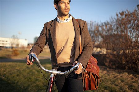Man with cell phone pushing bicycle Stock Photo - Premium Royalty-Free, Code: 614-06536821