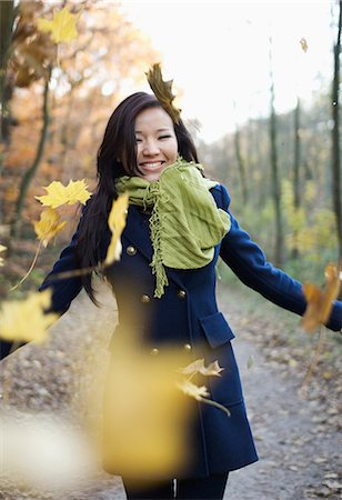Woman playing in autumn leaves Stock Photo - Premium Royalty-Free, Code: 614-06536865