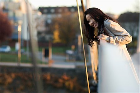 Woman leaning over bridge railing Stock Photo - Premium Royalty-Free, Code: 614-06536870