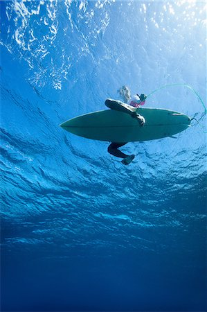 Low angle view of surfer in water Stock Photo - Premium Royalty-Free, Code: 614-06536885