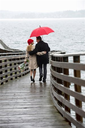 people with umbrellas in the rain - Couple walking on wooden pier in rain Stock Photo - Premium Royalty-Free, Code: 614-06536900