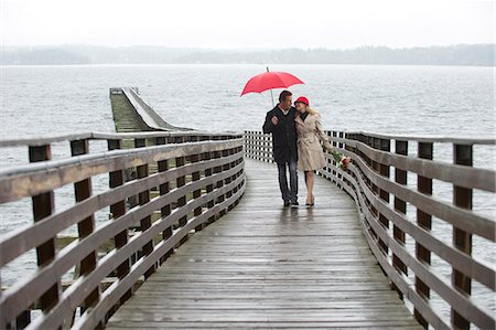 people with umbrellas in the rain - Couple walking on wooden pier in rain Stock Photo - Premium Royalty-Free, Code: 614-06536902