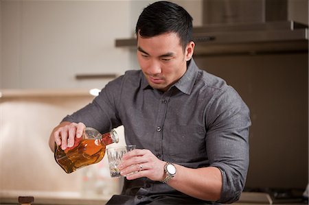self indulgence - Man pouring glass of whiskey in kitchen Stock Photo - Premium Royalty-Free, Code: 614-06536938