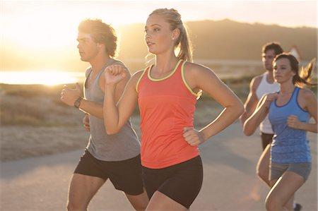 Friends running on beach Stock Photo - Premium Royalty-Free, Code: 614-06536960