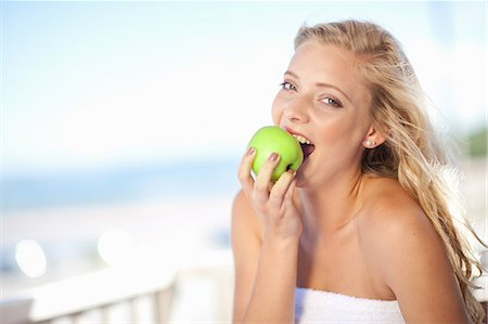 Woman eating apple outdoors Stock Photo - Premium Royalty-Free, Code: 614-06537017