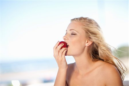 Woman eating apple outdoors Stock Photo - Premium Royalty-Free, Code: 614-06537018