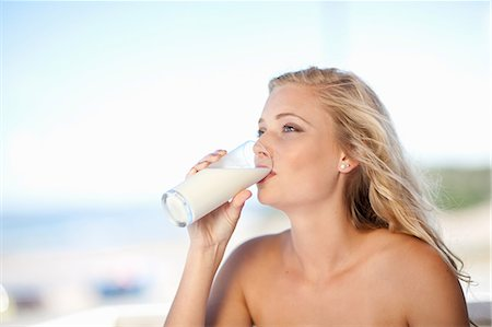 Woman drinking glass of milk outdoors Stock Photo - Premium Royalty-Free, Code: 614-06537019