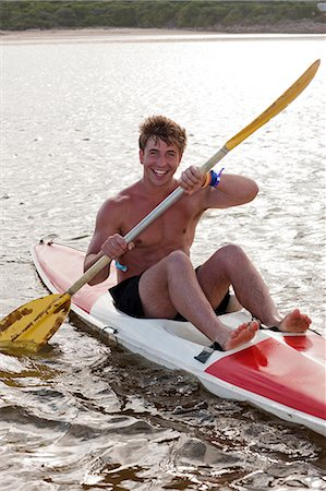 Smiling man rowing kayak in lake Stock Photo - Premium Royalty-Free, Code: 614-06537081