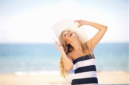 Woman wearing floppy hat on beach Stock Photo - Premium Royalty-Free, Code: 614-06537105