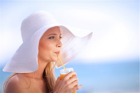 Woman in floppy hat drinking juice Stock Photo - Premium Royalty-Free, Code: 614-06537109