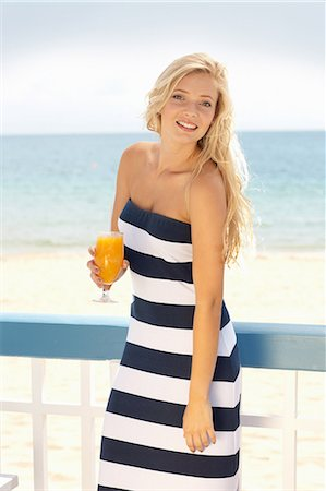 Woman drinking orange juice outdoors Stock Photo - Premium Royalty-Free, Code: 614-06537100