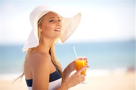 Woman in floppy hat having juice Stock Photo - Premium Royalty-Free, Code: 614-06537110