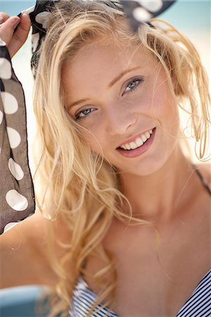 Smiling woman tying scarf in hair Stock Photo - Premium Royalty-Free, Code: 614-06537127