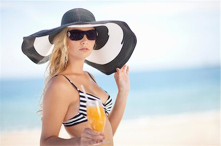 Woman in bikini and floppy hat on beach Stock Photo - Premium Royalty-Free, Code: 614-06537121