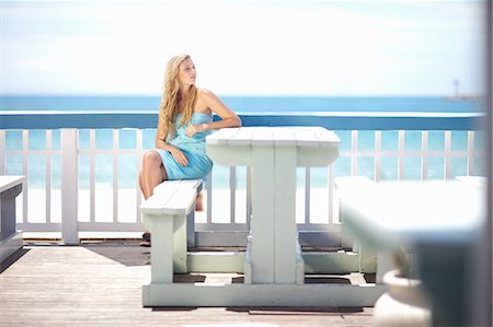 Woman sitting at table on deck Stock Photo - Premium Royalty-Free, Code: 614-06537137