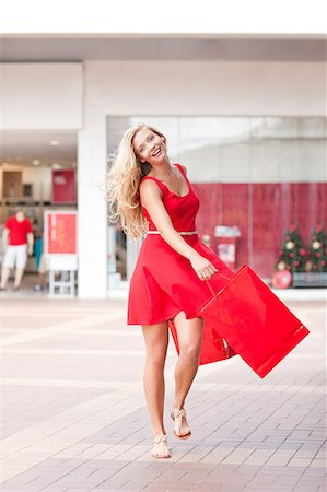 Woman carrying shopping bags in mall Stock Photo - Premium Royalty-Free, Code: 614-06537149