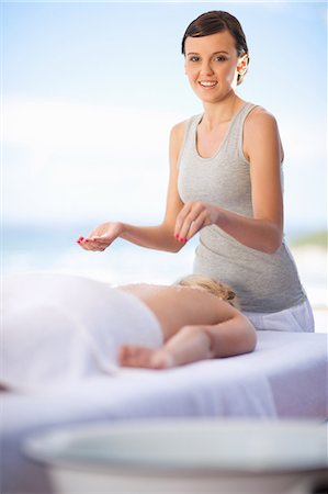 Woman giving massage on beach Stock Photo - Premium Royalty-Free, Code: 614-06537197