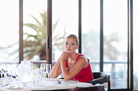 Woman sitting at restaurant table Stock Photo - Premium Royalty-Free, Code: 614-06537190