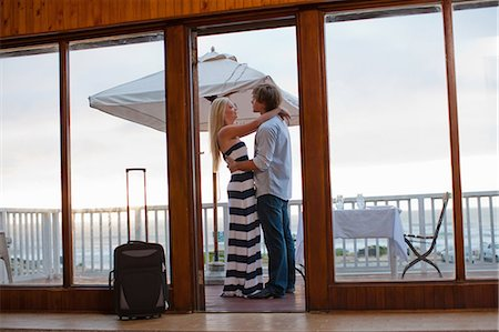exterior bar - Couple hugging on beachfront patio Stock Photo - Premium Royalty-Free, Code: 614-06537218