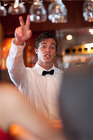 Waiter offering more drinks at bar Stock Photo - Premium Royalty-Free, Code: 614-06537213