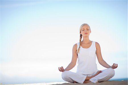 Woman meditating on beach Stock Photo - Premium Royalty-Free, Code: 614-06537234