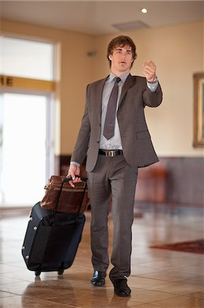 pulling - Businessman rolling luggage in lobby Stock Photo - Premium Royalty-Free, Code: 614-06537240