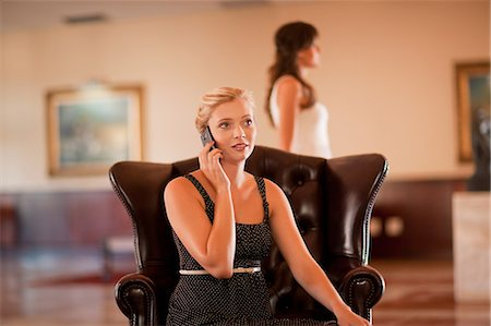 Woman talking on cell phone in lobby Stock Photo - Premium Royalty-Free, Code: 614-06537243