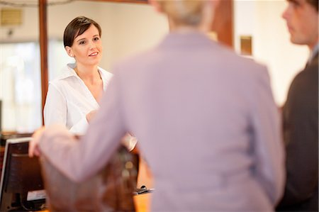 Hotel receptionist talking to guests Stock Photo - Premium Royalty-Free, Code: 614-06537254