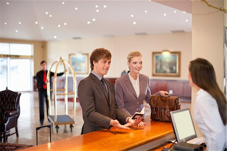 Businesswoman checking in to hotel Stock Photo - Premium Royalty-Free, Code: 614-06537250