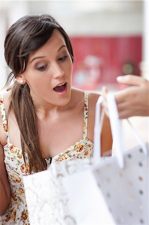 Woman looking in shopping bag Stock Photo - Premium Royalty-Free, Code: 614-06537290