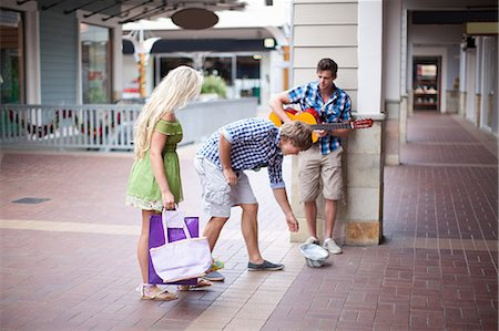 shopping mall - Man giving change to guitar player Stock Photo - Premium Royalty-Free, Code: 614-06537303