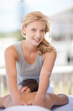 Smiling woman giving massage outdoors Stock Photo - Premium Royalty-Free, Code: 614-06537325