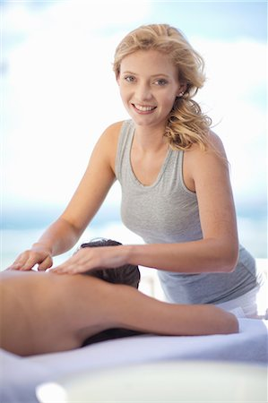 Smiling woman giving massage outdoors Stock Photo - Premium Royalty-Free, Code: 614-06537326