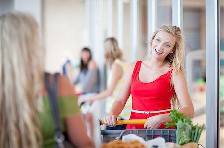 Women pushing shopping cart Stock Photo - Premium Royalty-Free, Code: 614-06537361