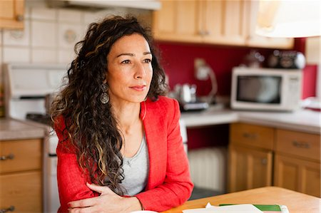 Smiling woman sitting in kitchen Stock Photo - Premium Royalty-Free, Code: 614-06537413